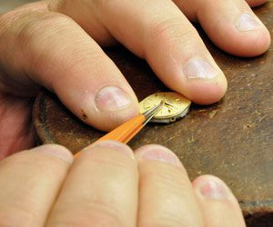 Norman Hege Jewelers   A pair of hands using a tool to do jewelry repair on a watch